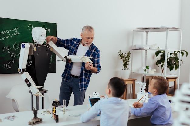 Futuristische entwicklungen. nette fleißige schüler, die sich notizen machen, während sie ihrem lehrer zuhören