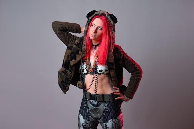 Futuristische mode, eine junge helle und attraktive frau mit rosa haaren, ein außergewöhnliches kostüm im kitsch-stil