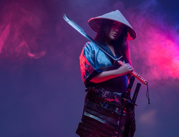 Futuristischer frauensamurai, der katana gegen hintergrund mit neonbeleuchtung und rauch hält.