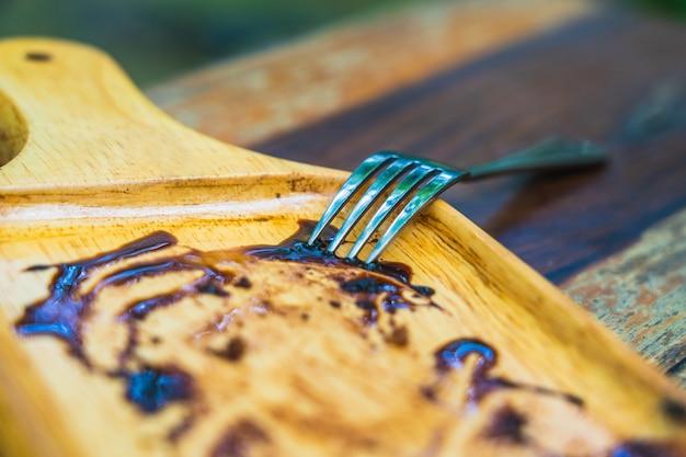 Gabel auf der hölzernen platte des leeren schokoladenkuchens