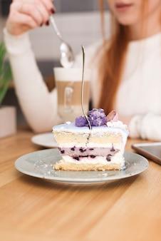 Gabel in leckeres schichtkuchenstück vor frau mit latte macchiato eingelegt