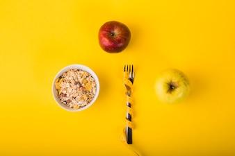 Gabel in Maßband zwischen Äpfeln und Flockenschüssel