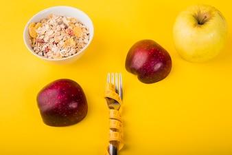 Gabel in Maßband zwischen Äpfeln und Schüssel Müsli
