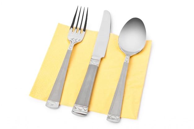 Gabel, messer und löffel auf tisch mit gelber serviette isoliert