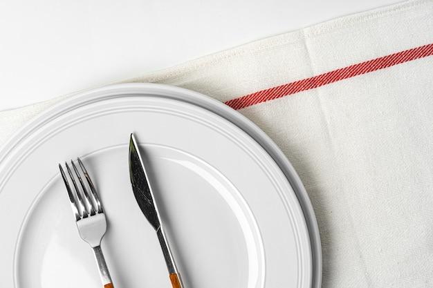 Gabel, messer und teller auf handtuch. auf weißem hintergrund isoliert. nahansicht.