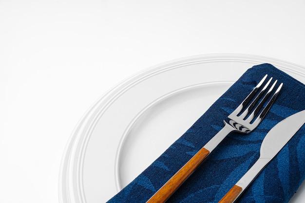 Gabel, messer und teller auf handtuch. auf weißem hintergrund isoliert. nahaufnahme. Premium Fotos