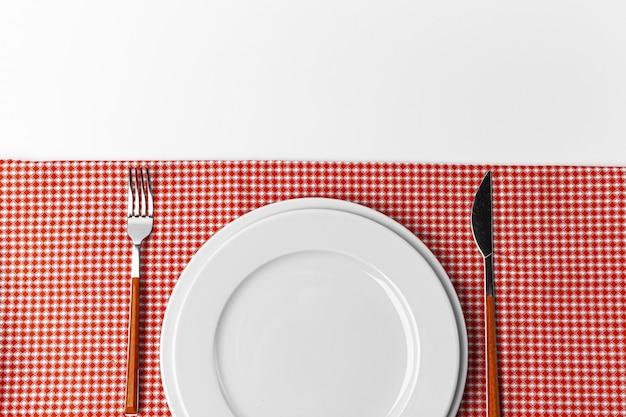 Gabel, messer und teller auf handtuch. auf weißem hintergrund isoliert. Premium Fotos