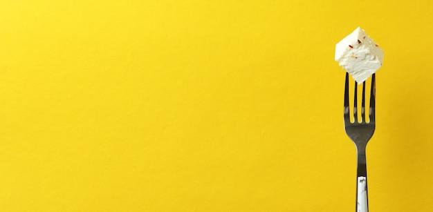 Gabel mit einem stück feta-käse auf gelber oberfläche