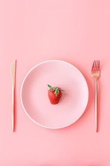 Gabel mit erdbeere auf teller draufsicht