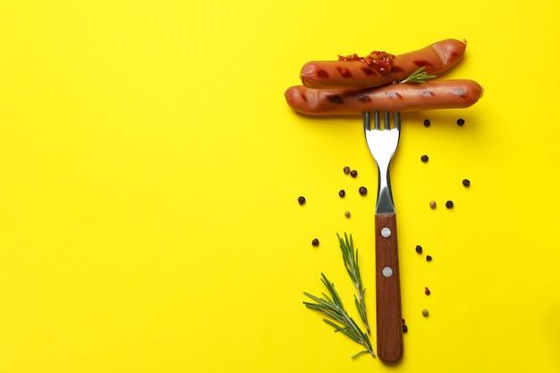 Gabel mit grillwurst auf gelber oberfläche