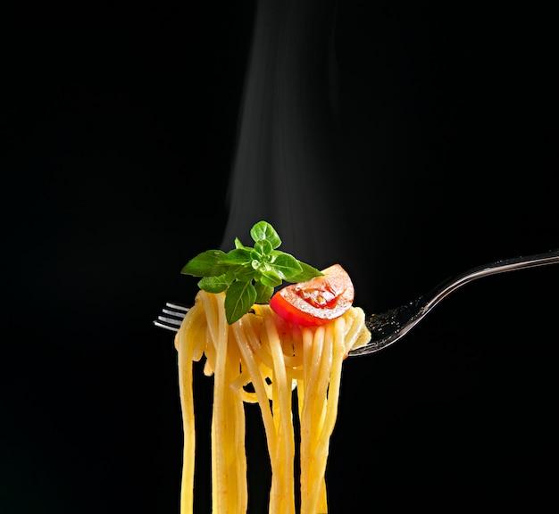 Gabel mit spaghetti, tomaten und basilikum auf schwarzem hintergrund isoliert. heiße spaghetti mit dampf
