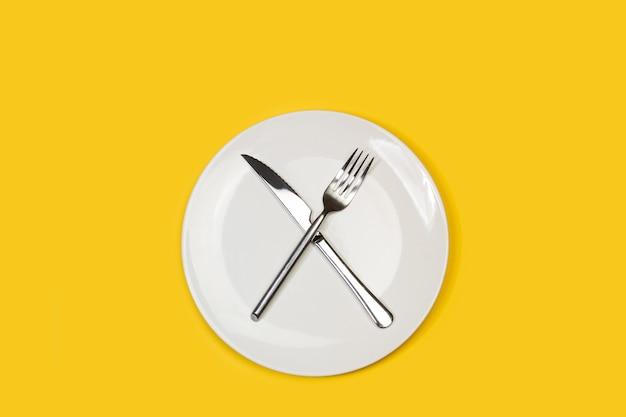 Gabel und messer auf einem weißen teller auf gelbem grund