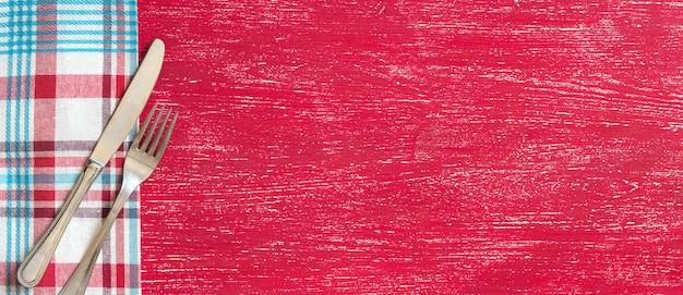 Gabel und messer auf serviette auf roter holztisch-draufsicht mit kopienraum