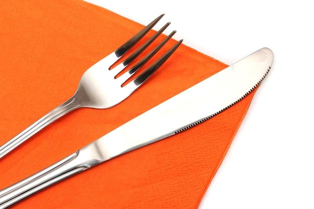 Gabel und messer in einem orangefarbenen tuch auf weiß