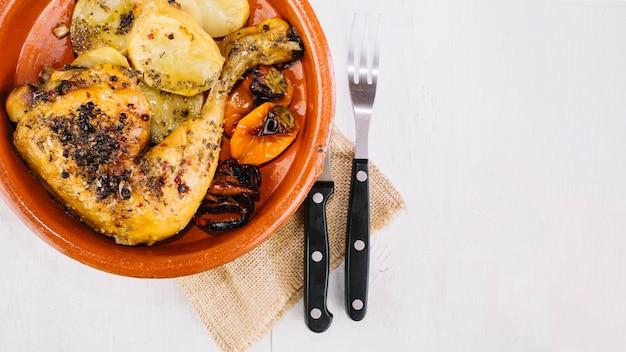 Gabel und messer nahe köstlichem hühnerbein