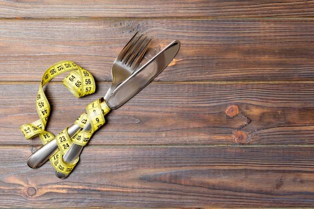 Gabel und messer und messendes band auf hölzernem hintergrund. draufsicht auf gewichtsverlust