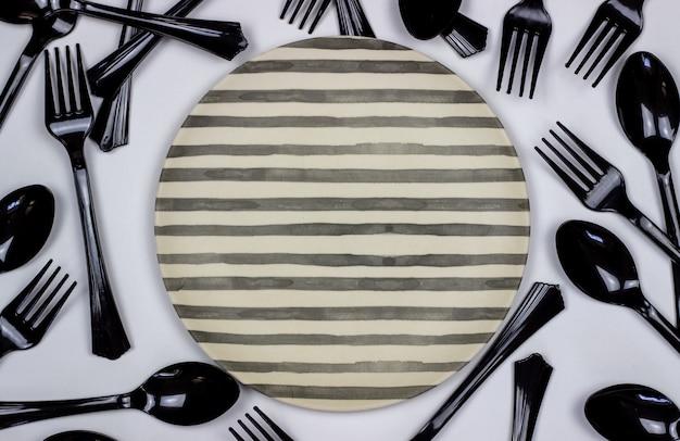 Gabeln und löffel neben der platte auf weiß