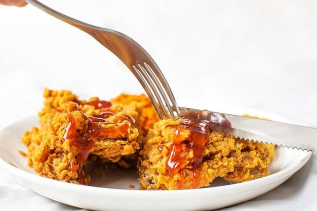 Gabeln und messer scheren knusprige gebratene hühnerbrust in einem weißen teller mit ketchup-sauce.