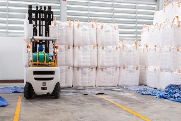 Gabelstapler befördert riesige taschen in einem großen lager.