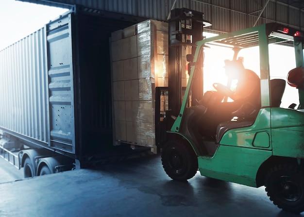 Gabelstapler-traktor, der paketkästen in den versandfrachtcontainer-lagerlogistiktransport lädt