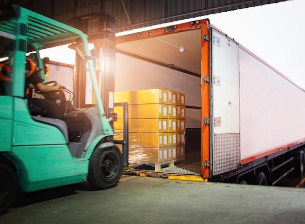 Gabelstapler-traktor, der paketkästen in frachtcontainer in der transportlogistik des docklagers lädt