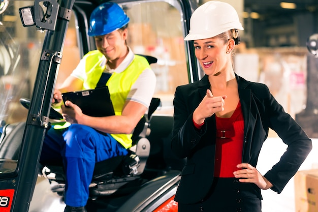 Gabelstaplerfahrer mit klemmbrett am lager der speditionsfirma, der weiblichen superblende oder des fahrdienstleiters, die auf den zuschauer zeigen