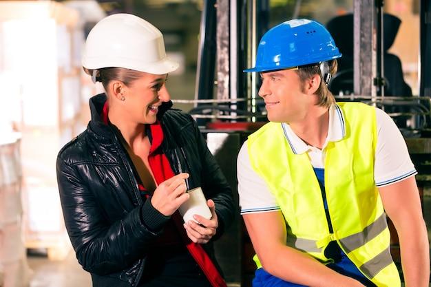 Gabelstaplerfahrer und weibliche mitarbeiter machen eine pause im lager der spedition
