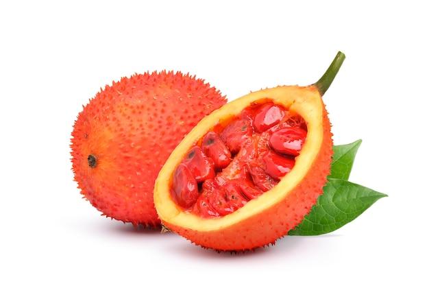 Gac-frucht mit halbiertem und grünem blatt isoliert auf weißer oberfläche