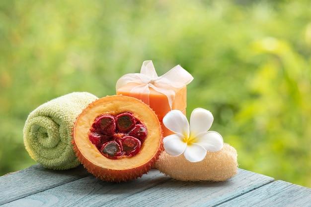 Gac-früchte und seife auf naturhintergrund.