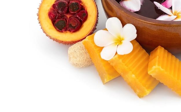 Gac-früchte und seife isoliert auf weißem hintergrund.