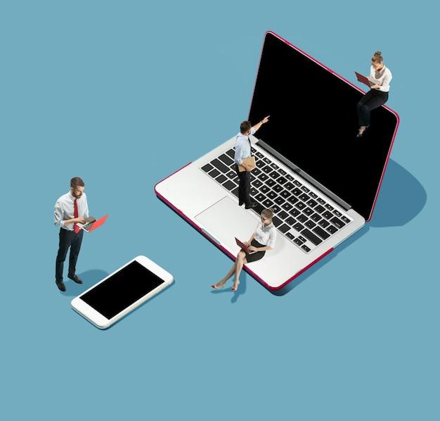 Gadget digitalisieren, umgeben. hohe betrachtungswinkel des kreativen modernen büros auf blauem hintergrund - große dinge und kleine arbeiter. büroarbeit, tägliche aufgabe, typische probleme und lifestyle-konzept. collage.