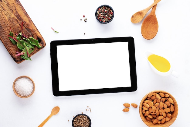 Gadget-modell leerer textraum auf weißem hintergrund mit gewürzen, öl, brett, salz und nuss. food-blog-rezept-kochbuch oder liefer-app mit kochzutat.