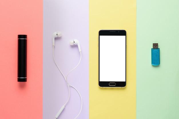 Gadgets. smartphone, powerbank, kopfhörer, flash-laufwerk auf mehrfarbigen streifen
