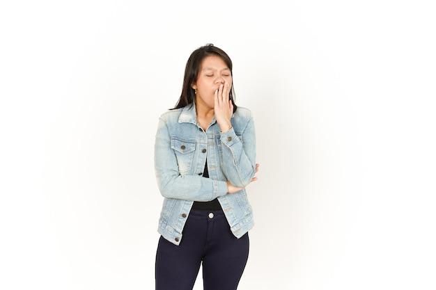 Gähnen der schönen asiatischen frau mit jeansjacke und schwarzem hemd isoliert auf weißem hintergrund