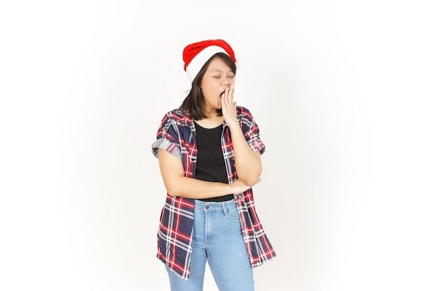 Gähnen der schönen asiatischen frau mit rotem kariertem hemd und weihnachtsmütze isoliert auf weißem hintergrund