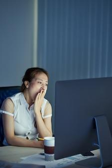 Gähnende junge geschäftsfrau, die den mund mit händen bedeckt, die müde sind, die ganze nacht am computer zu arbeiten