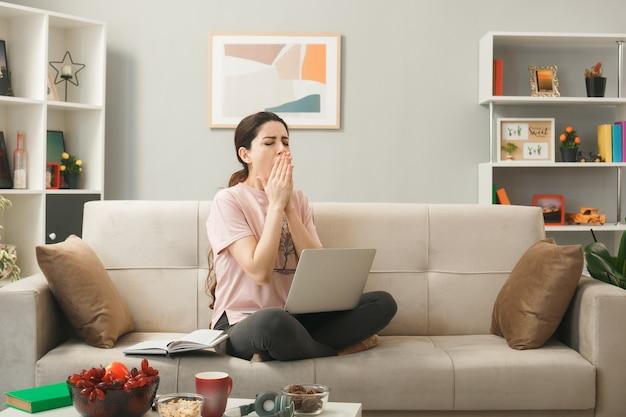 Gähnender bedeckter mund mit den händen junges mädchen, das auf dem sofa hinter dem couchtisch sitzt und den laptop im wohnzimmer benutzt