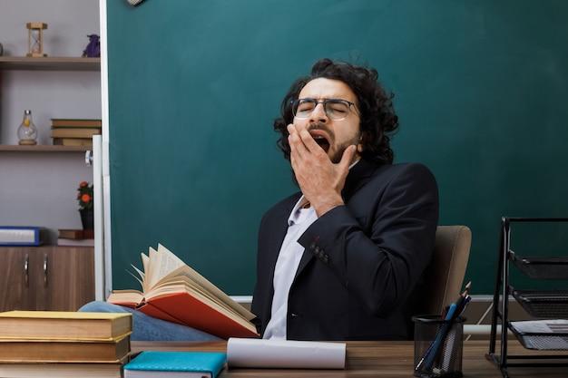 Gähnender bedeckter mund mit hand männlicher lehrer mit brille, der ein buch hält, das am tisch mit schulwerkzeugen im klassenzimmer sitzt