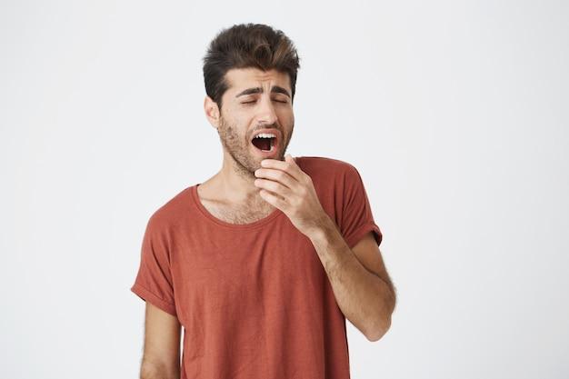 Gähnender junger mann mit bart und trendiger frisur, der die arbeit satt hat und seine hand hinter dem mund hält. studenten, die ein rotes t-shirt trugen, langweilten sich mit vorlesungen