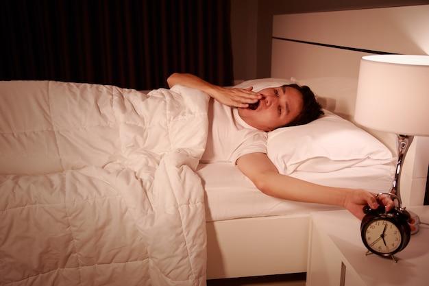 Gähnender mann, der durch einen wecker in seinem schlafzimmer am morgen geweckt wird