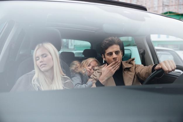 Gähnender mann, der im auto mit schlafender frau und tochter sitzt