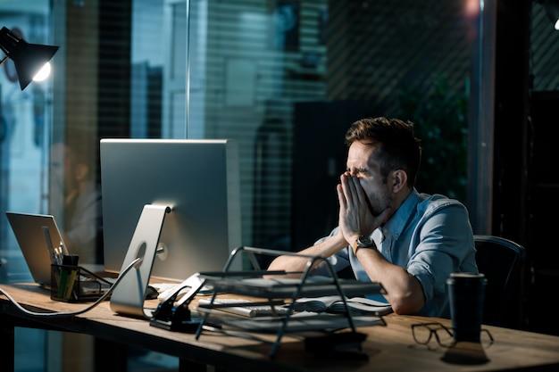 Gähnender müder mann, der stundenlang arbeitet