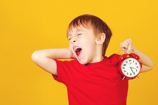 Gähnender schuljunge mit wecker auf gelbem hintergrund. lustiger junge gähnt weit. unterschiedliche tageszeiten und kinder planen konzept