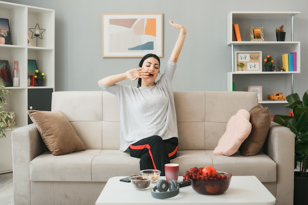 Gähnendes junges mädchen, das auf dem sofa hinter dem couchtisch im wohnzimmer sitzt, streckt den arm aus