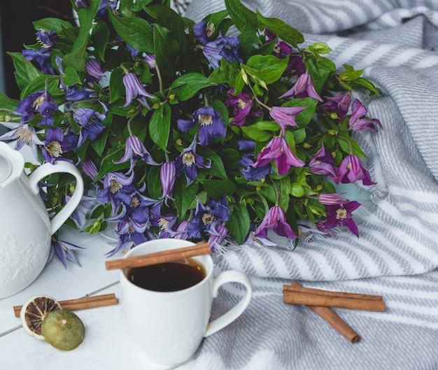 Gänseblümchen, eine tasse tee und zimtstangen