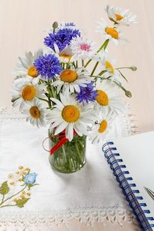 Gänseblümchen-kamille und kornblumen in einer vase auf einem holztisch mit einer serviette und einem notizbuch