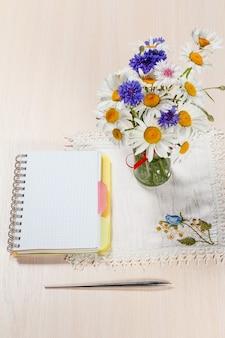 Gänseblümchen-kamille und kornblumen in vase auf einem holztisch mit einem notizbuch und einem stift