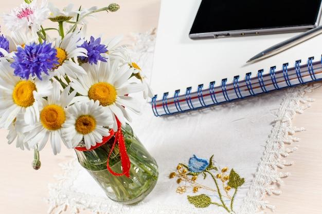 Gänseblümchen-kamille und kornblumen in vase auf einem holztisch mit smartphone, heft und stift Premium Fotos