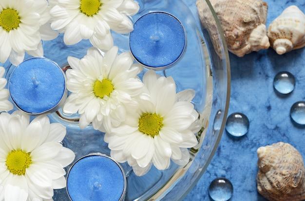 Gänseblümchen und kerzen im wasser über dem meer