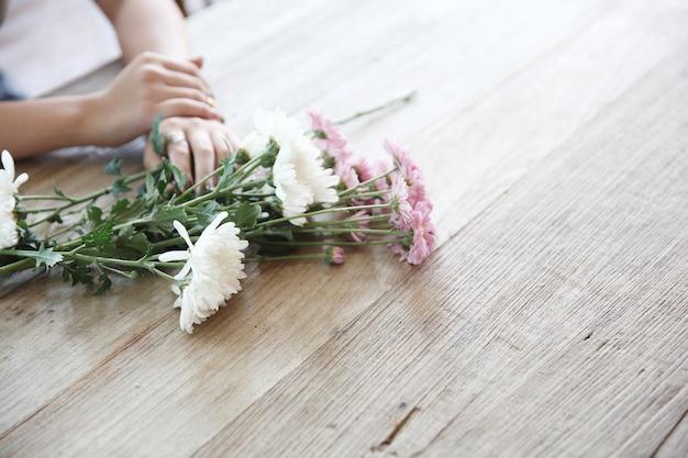 Gänseblümchenblumen auf holz mit mädchenhand